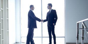 窓際で握手するビジネスマン